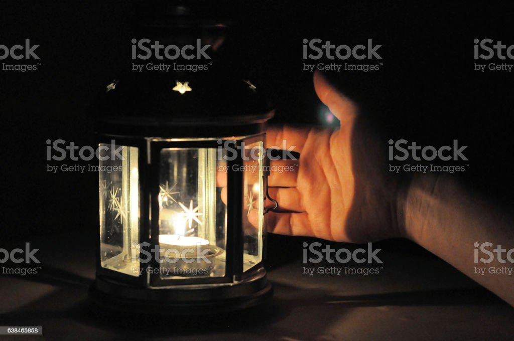 Hand illuminated wirt light from candle lantern in dark stock photo