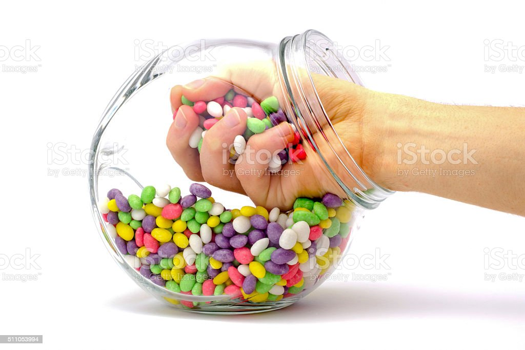 hand in a jar with colored candies isolated stock photo