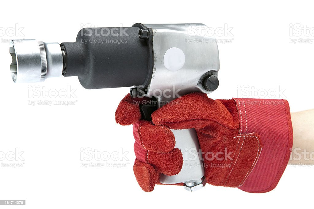 Hand in a red working glove holding an air impact wrench stock photo