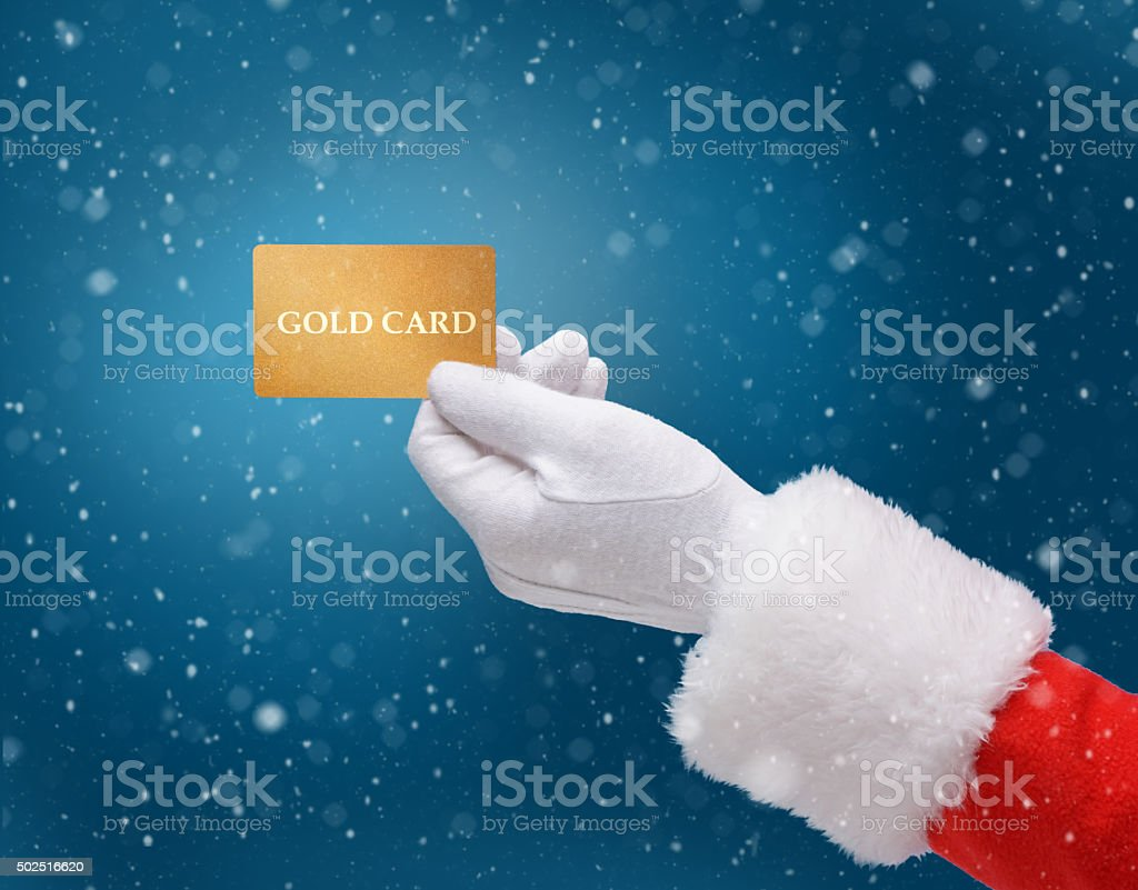 Hand in costume Santa Claus is holding gold card stock photo