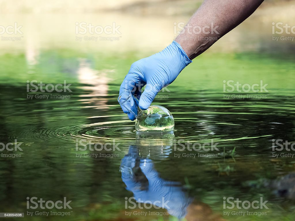 Hand in glove collects water to explore stock photo
