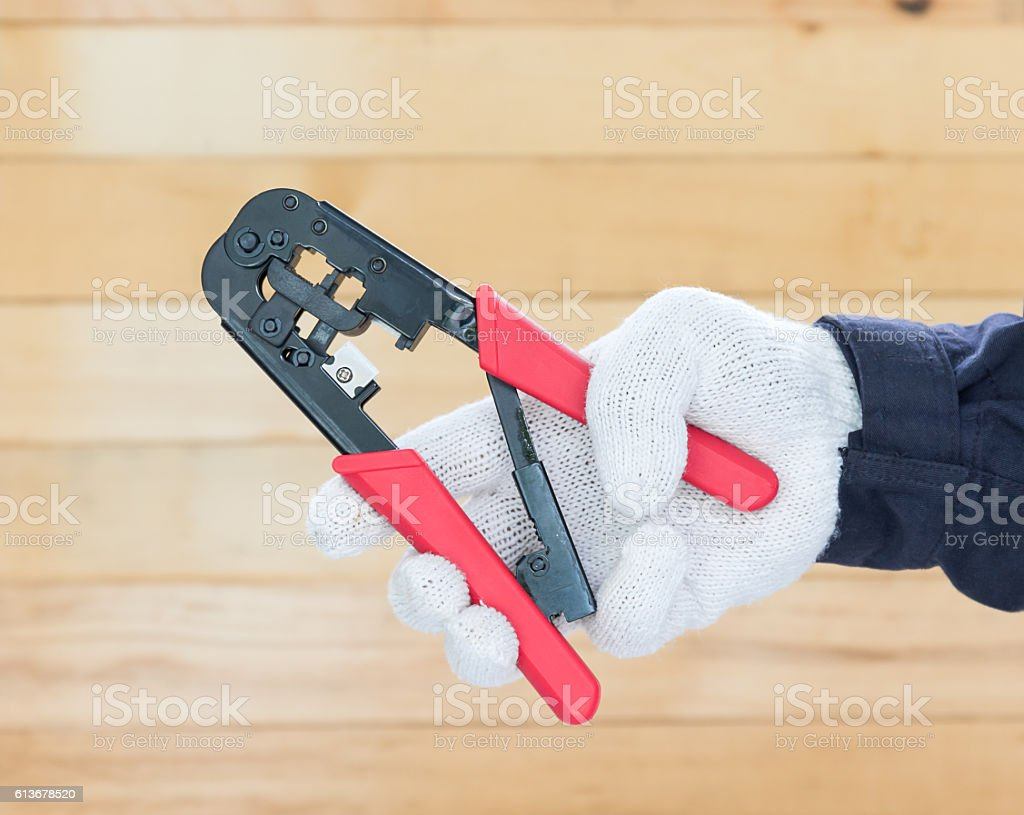 Hand in glove hold wire stripper stock photo