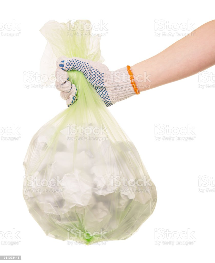 Hand in glove holding a bag of garbage on white stock photo