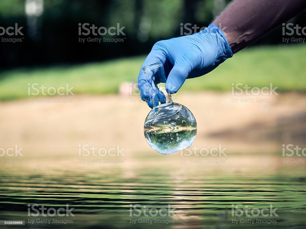 Hand in glove holding a retort with clear water stock photo