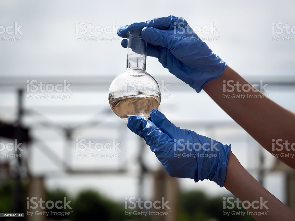 Hand in glove holding a retort with muddy water stock photo