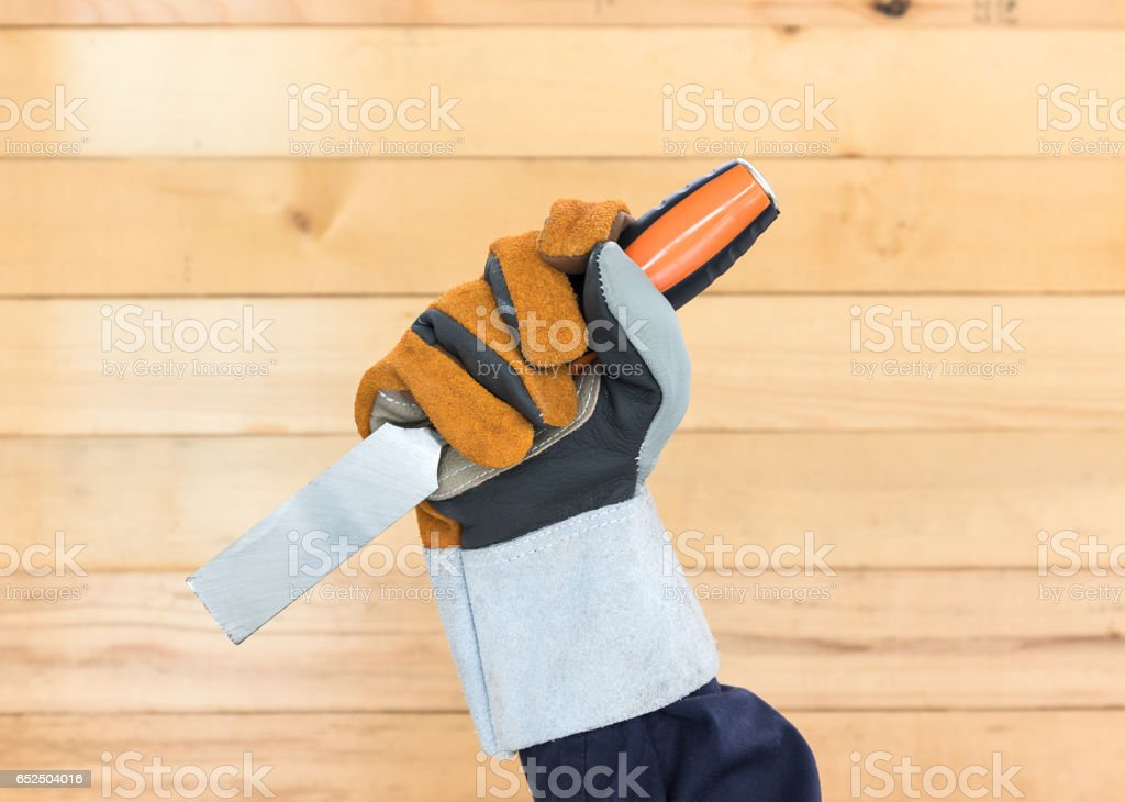 Hand in glove holding chisel stock photo