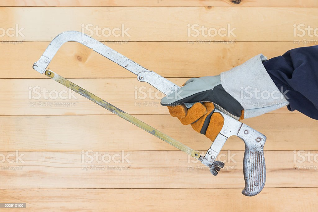 Hand in glove holding hack saw stock photo