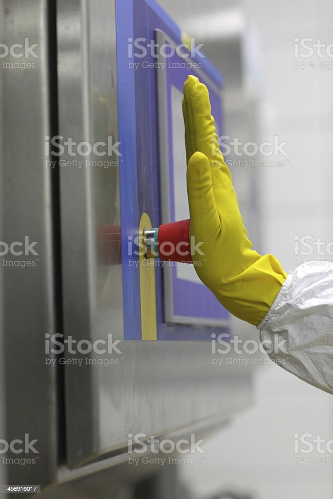 hand in glove touching technology button at control panel stock photo