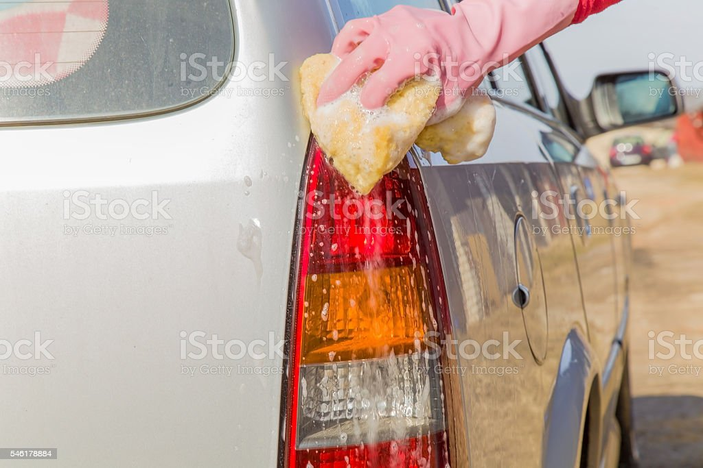 Hand in  glove washing a cars back lamp with sponge. stock photo