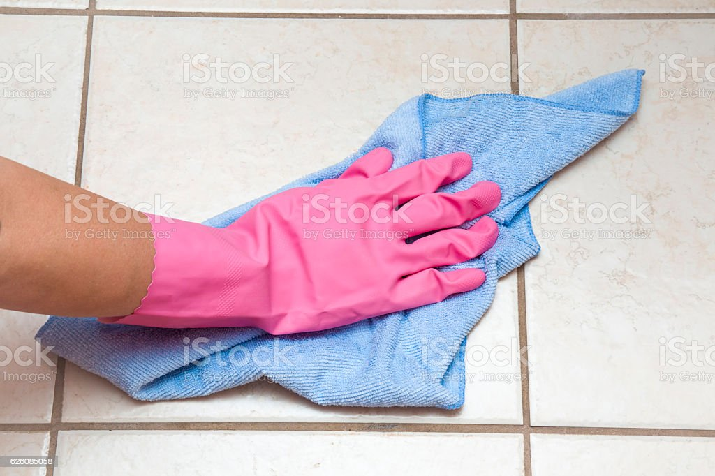 Hand in glove wiping tiles with rag in the bathroom. stock photo