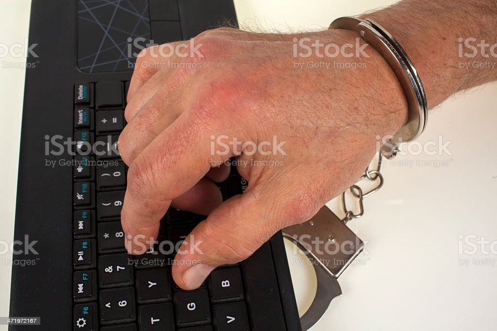 Hand in handcuffs and keys stock photo
