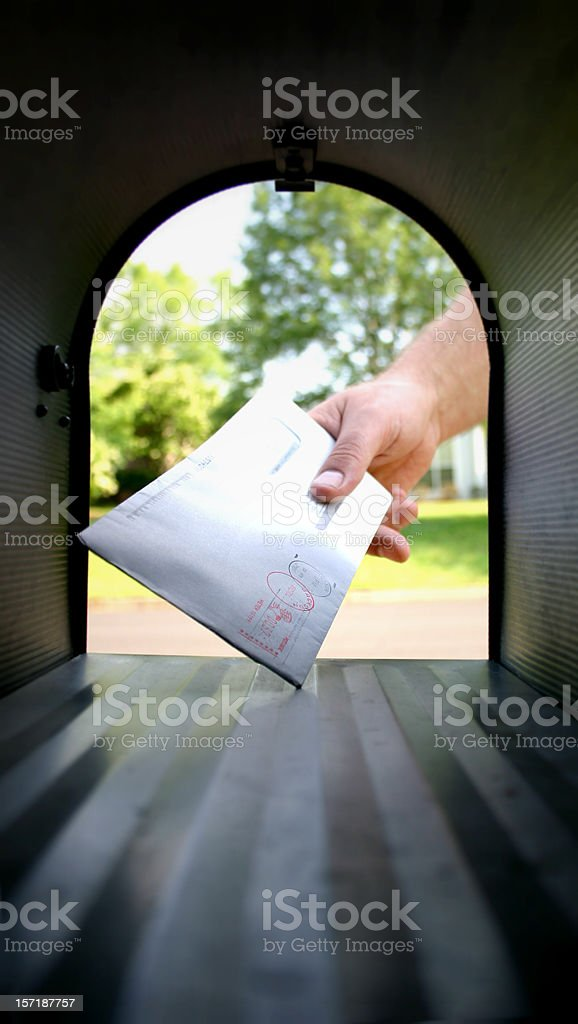 Hand in Mailbox getting Mail stock photo