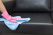 Hand in pink protective glove wiping leather sofa with cloth.