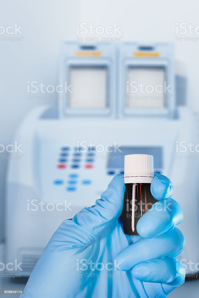 Hand in protective glove holds sample, blurred laboratory backgr stock photo