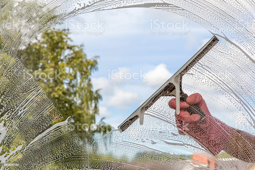 Hand in protective glove washing and cleaning window. stock photo