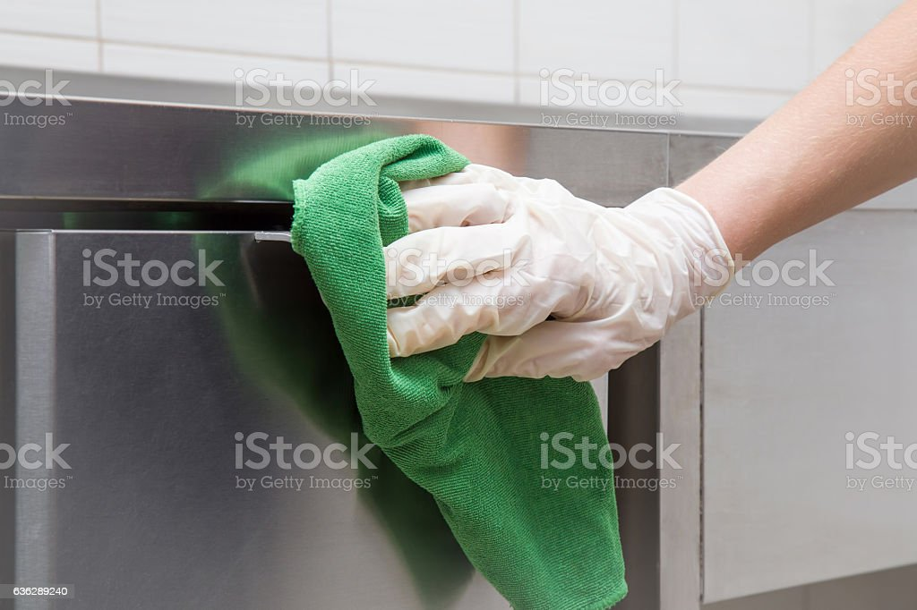 Hand in protective glove with rag cleaning kitchen equipment. stock photo