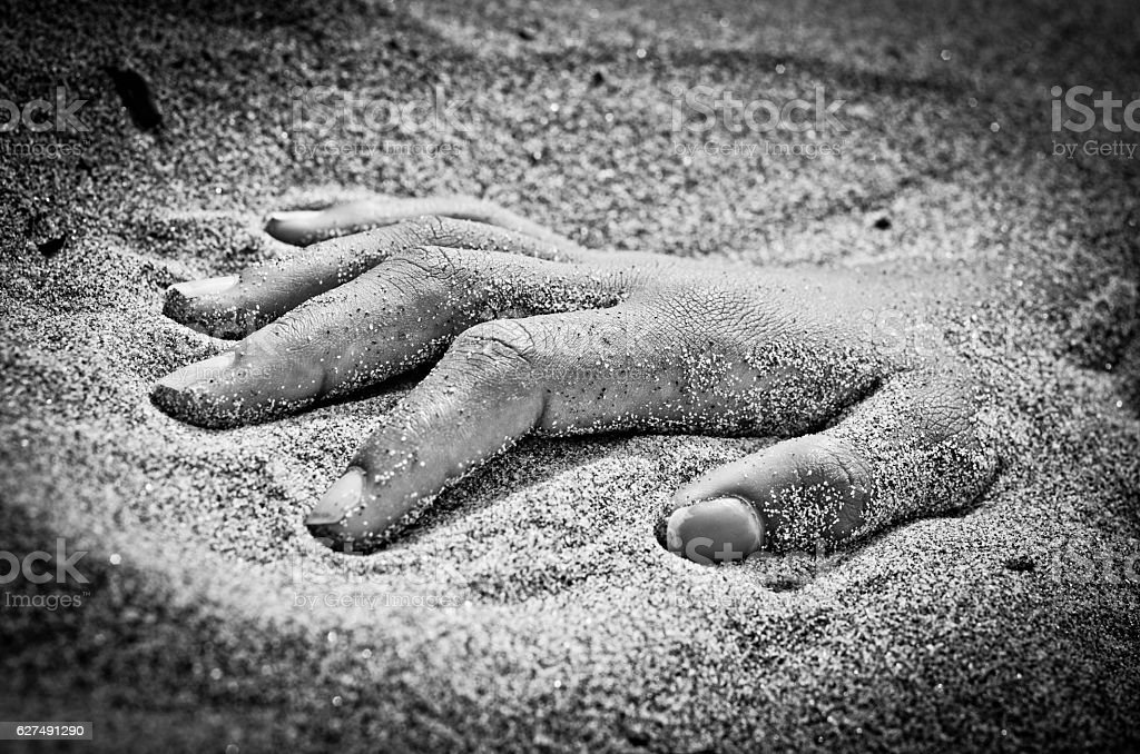 hand in rigor mortis on the beach stock photo