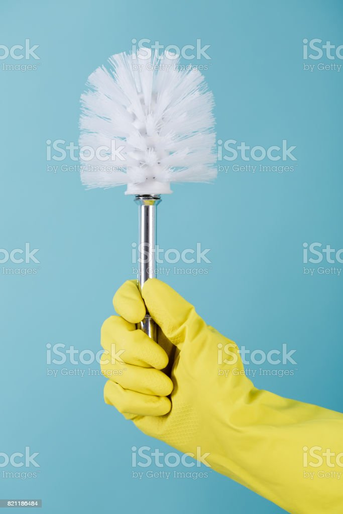 Hand in rubber yellow glove holds brush for toilet on blue background. cleaning. stock photo