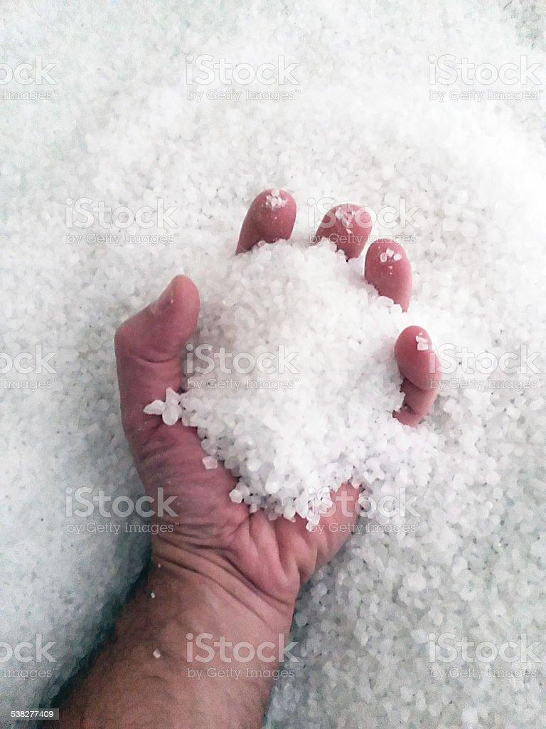 Hand in sea salt - Cave salt stock photo