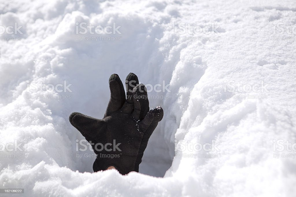 Hand in snow reaching for help stock photo