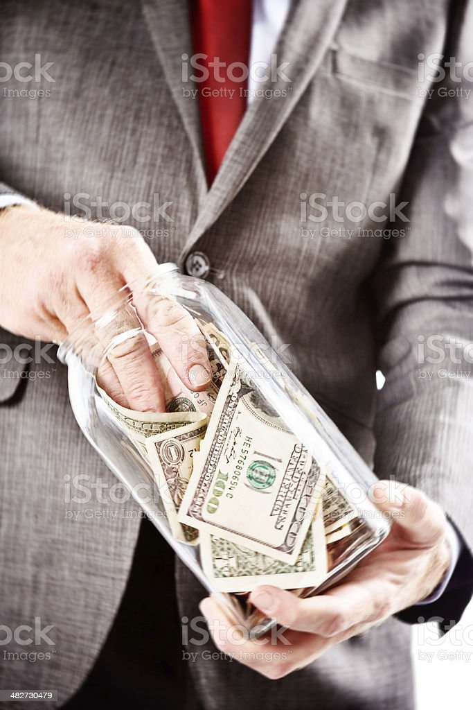Hand in the cookie jar! Businessman taking dollars from bottle stock photo