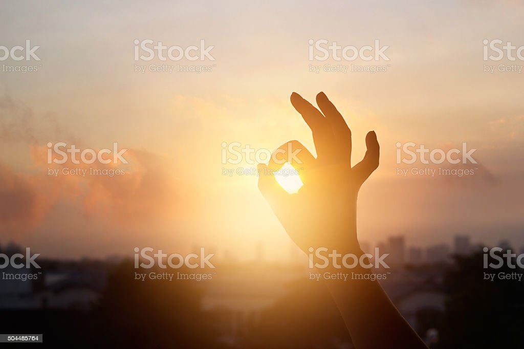 hand in the sunset, one sign of meditation in buddhism stock photo