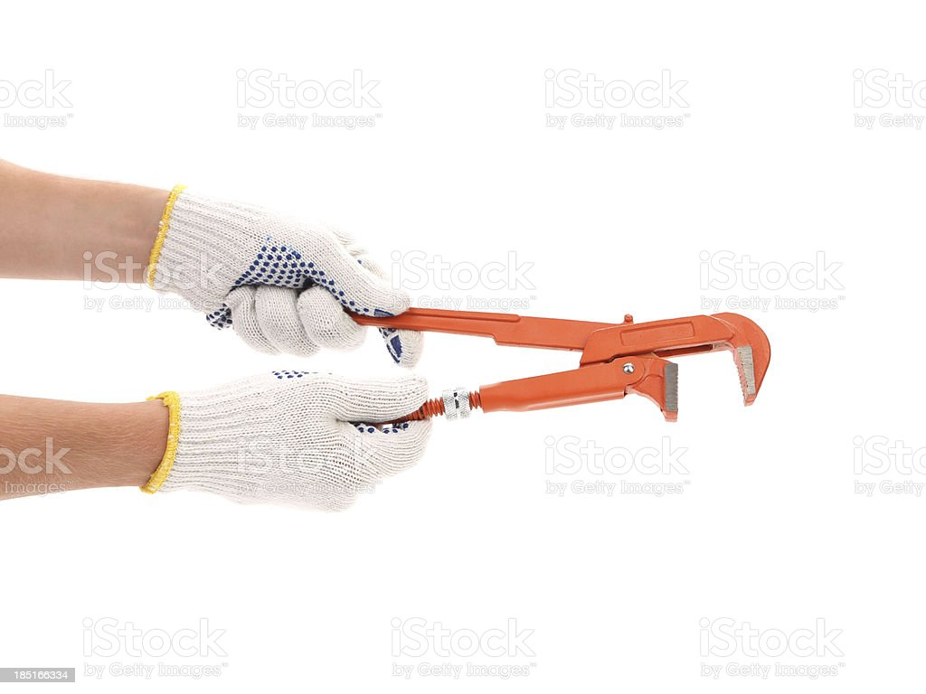 Hand in white gloves holding wrench. royalty-free stock photo