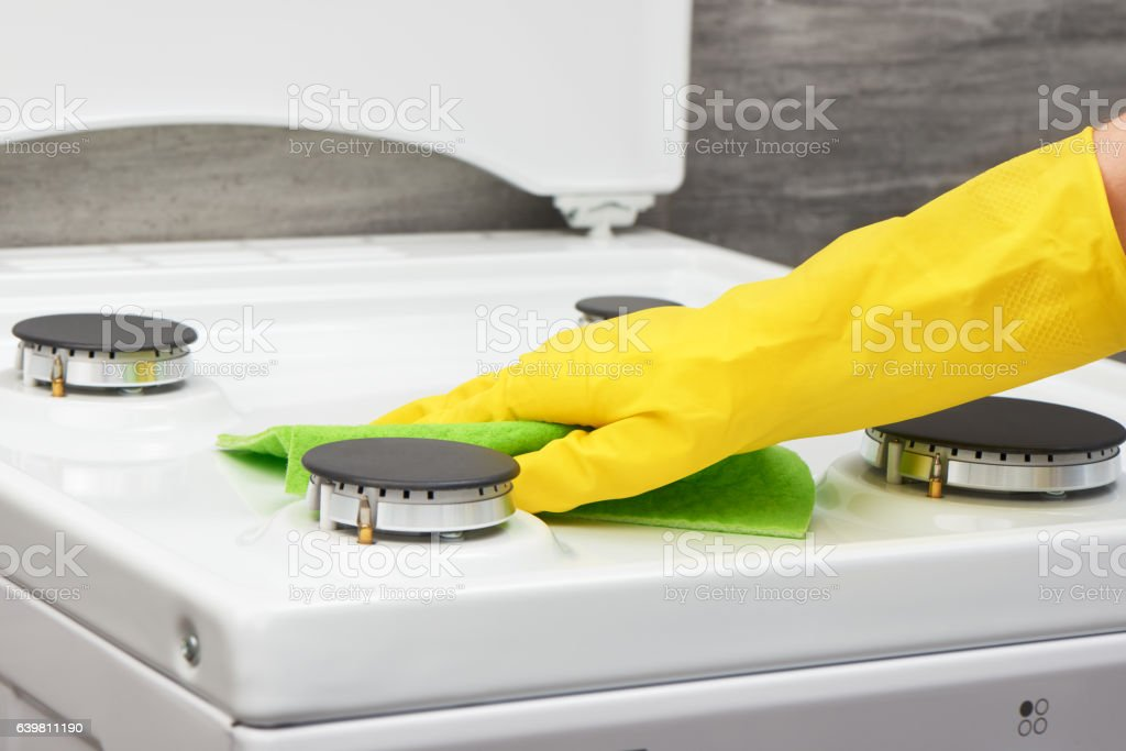 Hand in yellow glove cleaning white stove with green rag stock photo