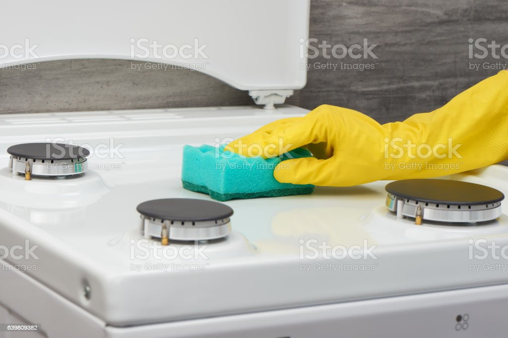 Hand in yellow glove cleaning white stove with green sponge stock photo