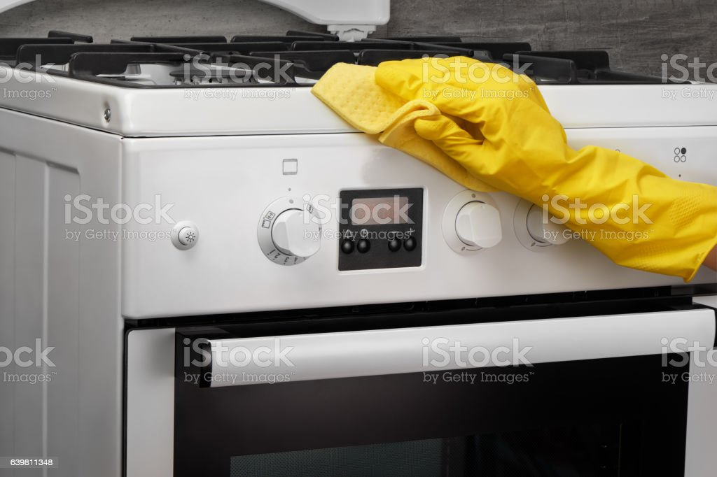 Hand in yellow glove cleaning white stove with rag stock photo