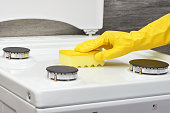 Hand in yellow glove cleaning white stove with sponge