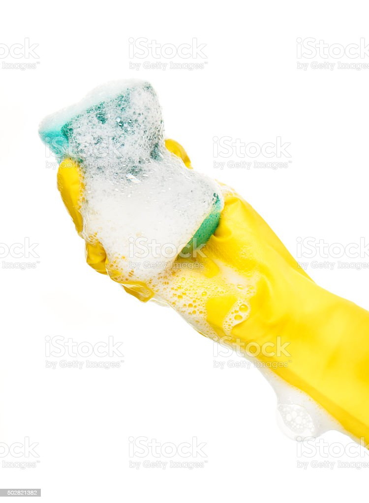 Hand in yellow glove holding green cleaning sponge in foam stock photo