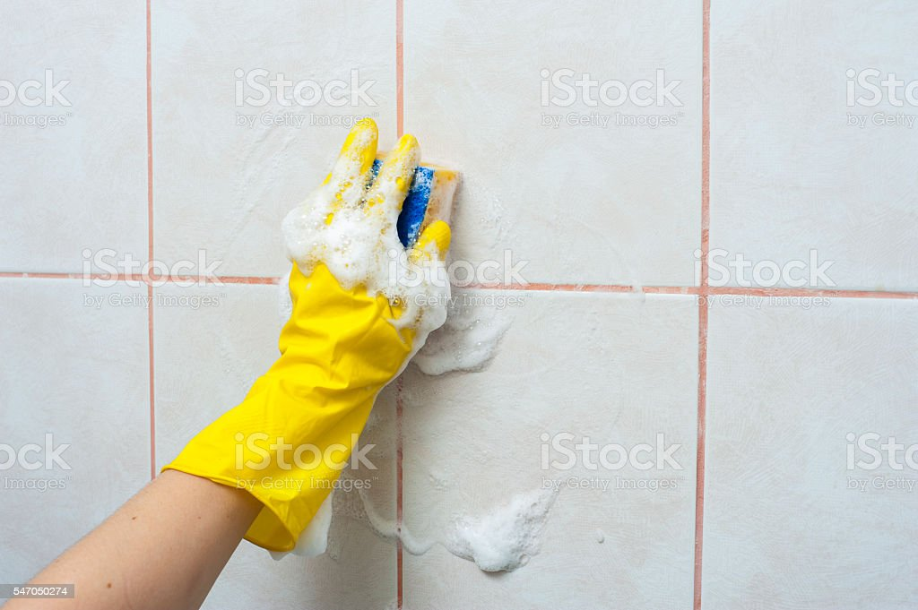 Hand in yellow glove with sponge washing the tile stock photo