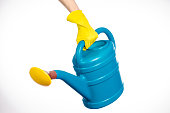 hand in yellow rubber gloves holding a plastic watering can