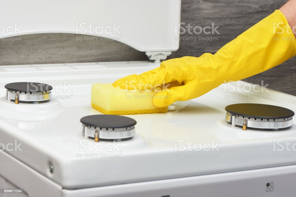 Hand in yellowglove cleaning white stove with yellow sponge stock photo