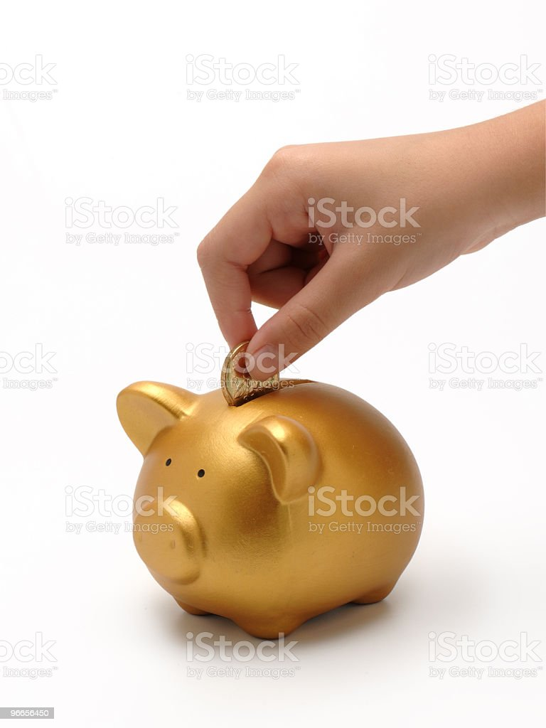 Hand inserting a gold coin into a gold piggy bank royalty-free stock photo