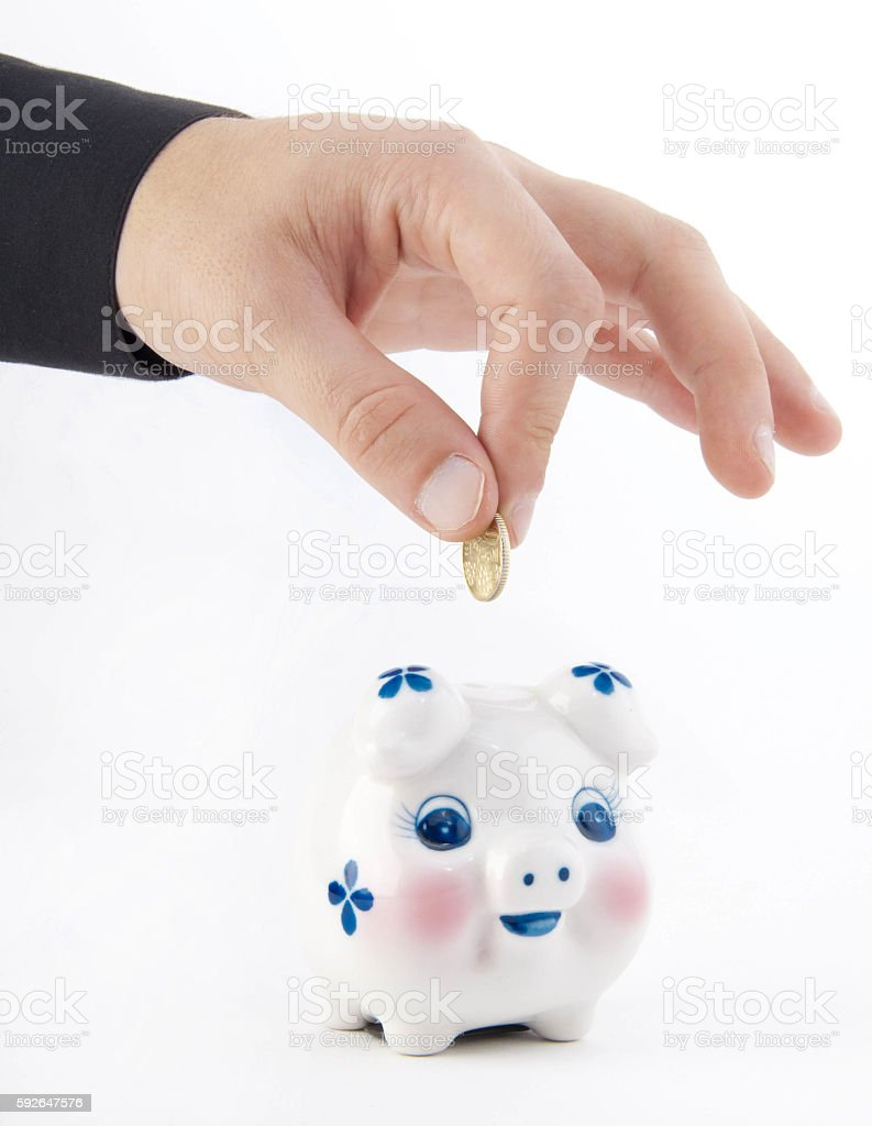 Hand inserting coin into piggy-bank stock photo