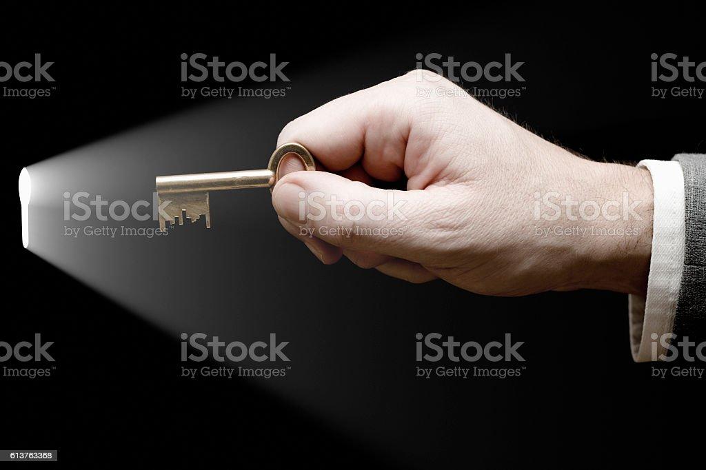 Hand inserting key in keyhole stock photo