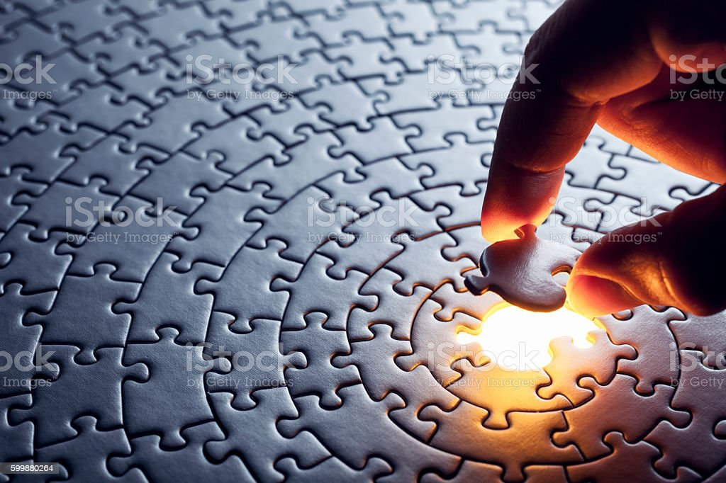 Photography of a hand inserting a missing puzzle piece.