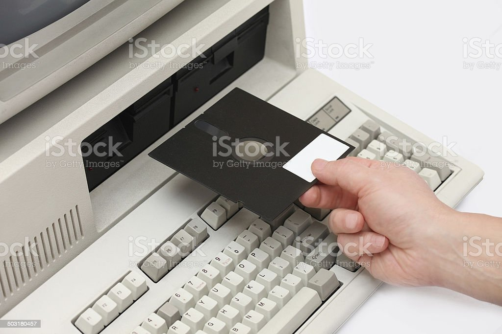 Hand inserting old floppy disk drive into vintage eigthies computer stock photo