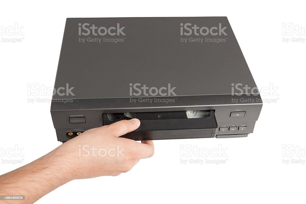 hand inserts videocassette in videorecorder isolated on white background stock photo