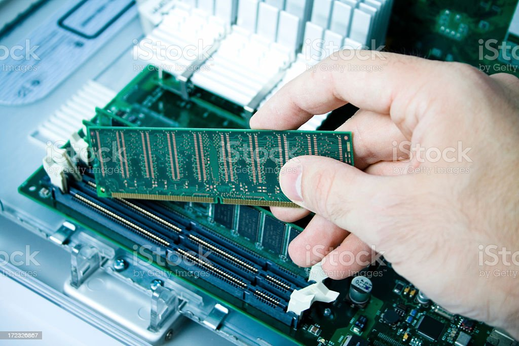 A hand installing a ram in a PC stock photo