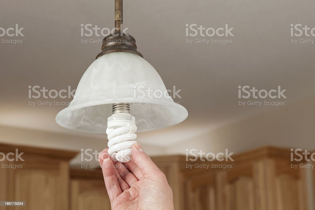 Hand Installing Compact Florescent Light Bulb stock photo