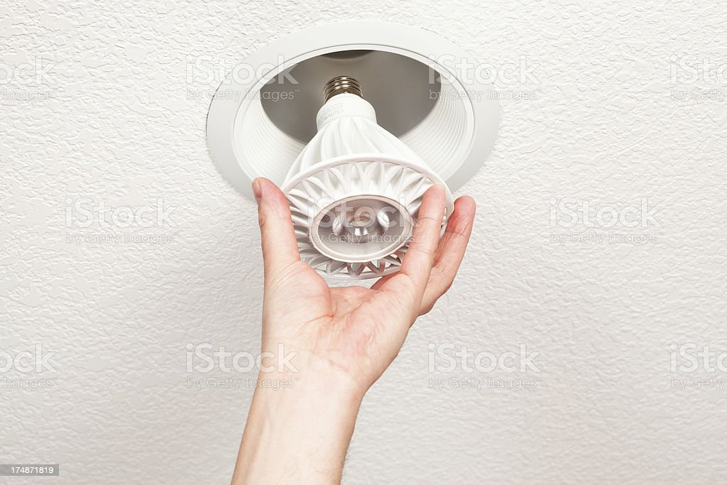 Hand Installing LED Light Bulb into Ceiling Fixture stock photo