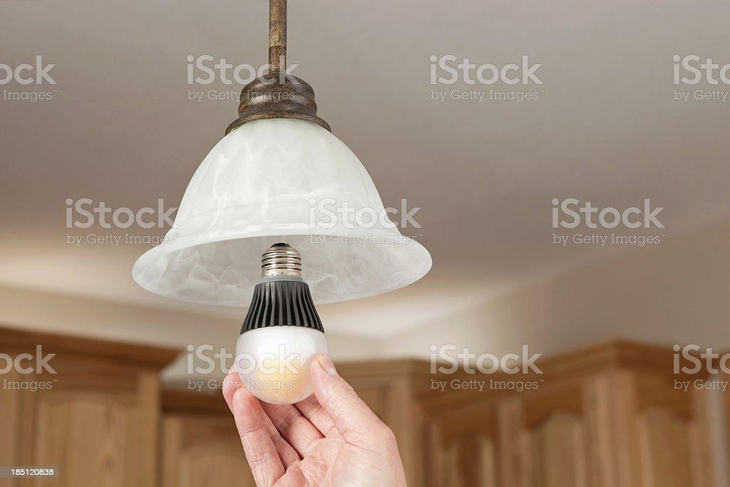 Hand Installing LED Light Bulb stock photo