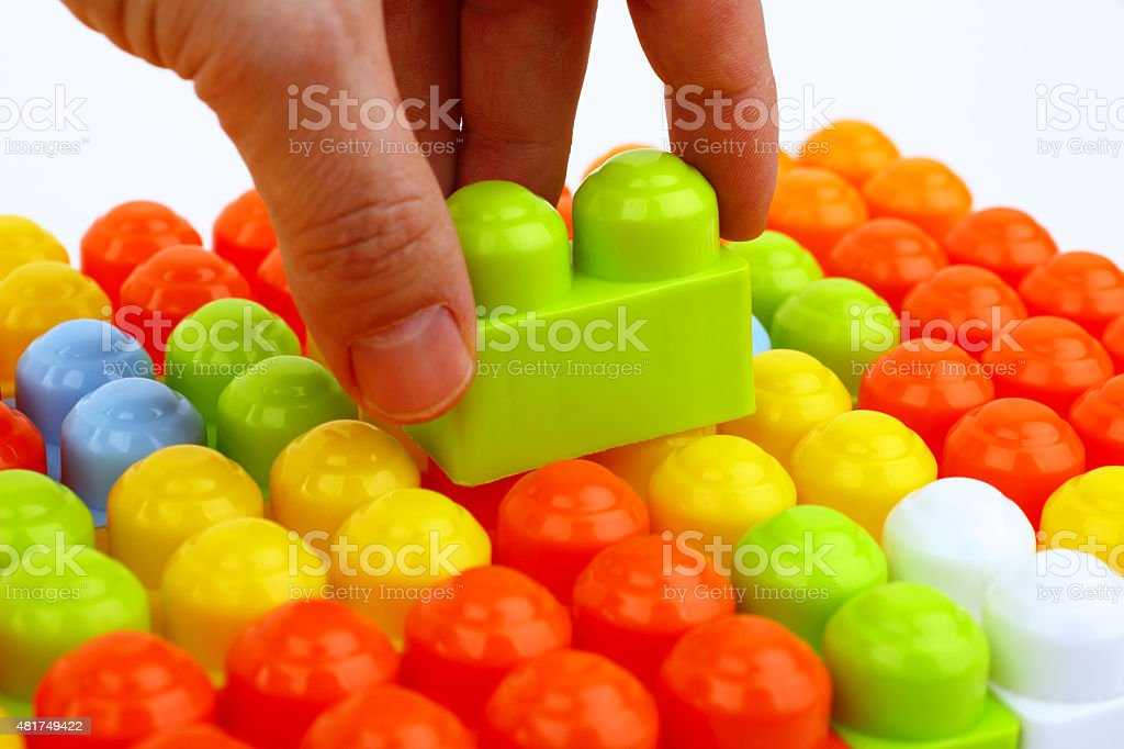 Hand is buildings with toy bricks stock photo