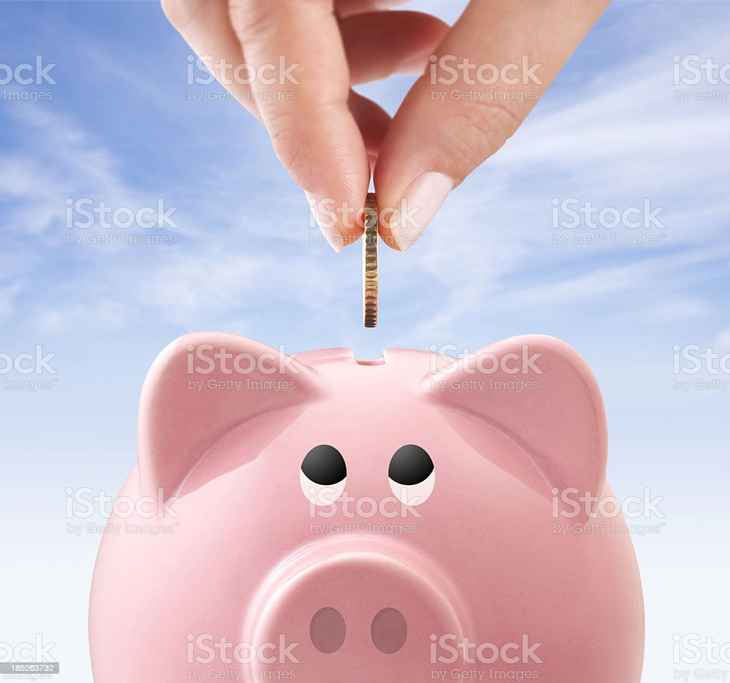 Hand is inserting a coin into piggy bank royalty-free stock photo