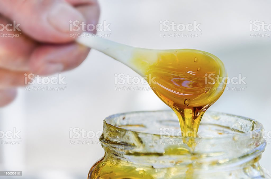 hand is pouring honey from porcelan spoon drizzler stock photo