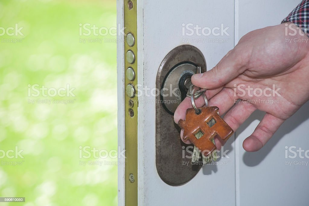Hand, Keys, key ring in house shape, security door. stock photo