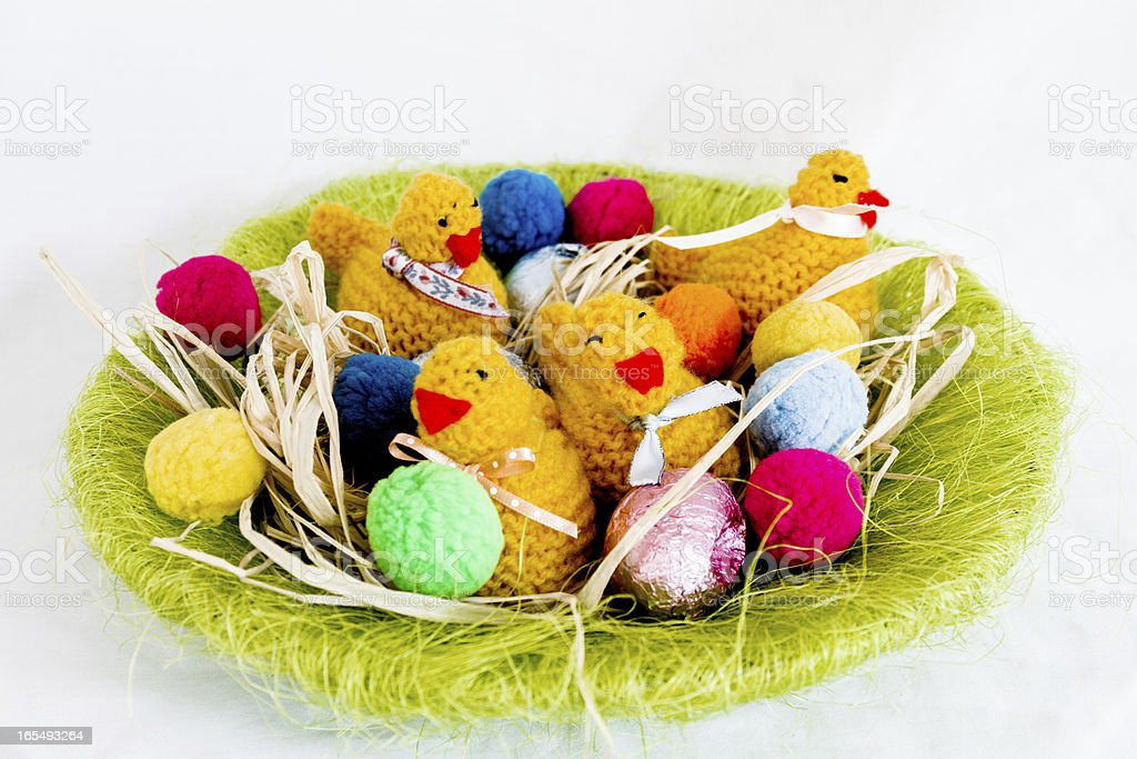 Hand knitted chicks and chocolate eggs in a green nest royalty-free stock photo